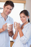 Portrait of a couple drinking tea. In their kitchen Stock Photos