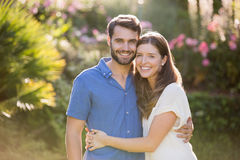 Portrait of couple embracing. While standing at park stock images
