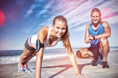 Portrait of couple exercising on sand Royalty Free Stock Images
