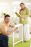 Portrait of couple fixing baby bed Royalty Free Stock Photos