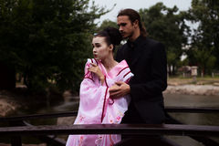 Portrait of couple - geisha girl in tender pink kimono and caucasian man. Portrait of couple - geisha girl in tender pink kimono and caucasian men - in park near Royalty Free Stock Images