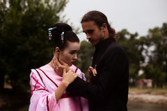 Portrait of couple - geisha girl in tender pink kimono and caucasian man. Portrait of couple - geisha girl in tender pink kimono and caucasian men - in park near Stock Image