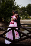 Portrait of couple - geisha girl in tender pink kimono and caucasian man. Portrait of couple - geisha girl in tender pink kimono and caucasian men - in park near Royalty Free Stock Photos