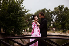 Portrait of couple - geisha girl in tender pink kimono and caucasian man. Portrait of couple - geisha girl in tender pink kimono and caucasian men - in park near Royalty Free Stock Image