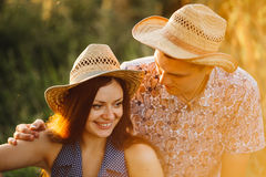 Portrait of couple of girlfriend and boyfriend in hats sitting on grounds in meadow, having fun, smiling and touching each other. Stock Images