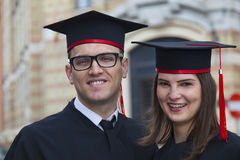 Portrait of a Couple in the Graduation Day. Outdoor portrait of a young couple of students in the graduation day near the university building Stock Photos