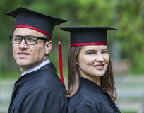 Portrait of a Couple in the Graduation Day. Outdoor portrait of a young couple of students in the graduation day in a park Stock Images