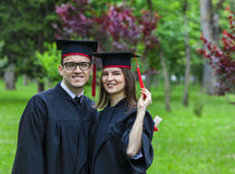 Portrait of a Couple in the Graduation Day. Outdoor portrait of a young couple of students in the graduation day in a park Stock Photos