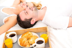 Portrait of a couple having breakfast in bed Royalty Free Stock Images