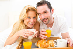 Portrait of a couple having breakfast in bed Royalty Free Stock Image