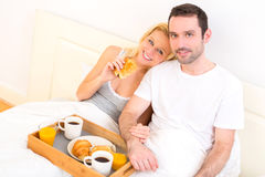 Portrait of a couple having breakfast in bed Royalty Free Stock Photography