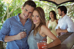 Portrait of couple having a glass of cocktail at counter. In restaurant stock images