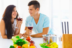 Portrait of a couple having a glass of red wine while cooking Royalty Free Stock Photos