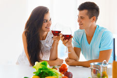 Portrait of a couple having a glass of red wine while cooking Stock Images