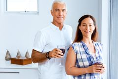 Portrait of a couple having a glass of red wine. At home stock photography