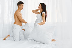 Portrait of couple having a pillow fight in bed Stock Photo