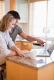 Portrait of a couple having tea while using a laptop Royalty Free Stock Photography