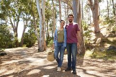 Portrait Of Couple Hiking Along Forest Path Together Stock Photo
