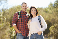 Portrait Of Couple Hiking In Countryside. Wearing Backpacks Stock Photo