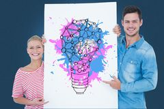 Portrait of couple holding billboard with colorful light bulb icon against blue background Stock Photo