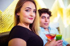 Portrait of couple holding cocktail glasses. Portrait of young couple holding cocktail glasses at nightclub royalty free stock image