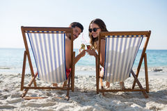 Portrait of couple holding drinks while relaxing on deck chairs at beach Royalty Free Stock Photo