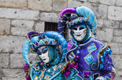 Portrait of a Couple of Jesters. Annecy, France, February 23, 2013: Portrait of an Unidentified couple disguised in blue jesters costumes pose in front of a Royalty Free Stock Image