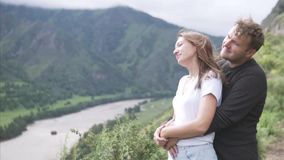 A man hugs a woman and they look in one direction at a beautiful view from the mountain. Portrait of couple kissing and hugging in mountains Slow motion. Young stock footage
