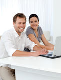 Portrait couple with a laptop at a table Stock Images