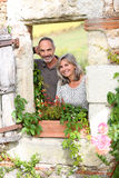 Portrait of couple looking through window Stock Photography