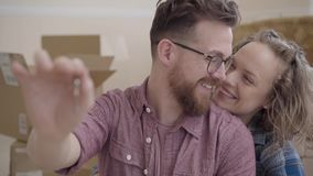 Portrait of a couple in love, they just bought a house and moving. Bearded man in glasses shows the key, looking at his. Wife then in camera, smiling. Cute stock video footage