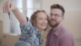 Portrait of a couple in love, they just bought a house and moving. Woman extends a hand with keys to the camera, man. Portrait a couple in love, they just bought stock video footage