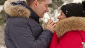 Portrait of a couple in love in the winter forest. A caring man warms his wife`s hands in the winter on the street in a snow-covered Park stock footage