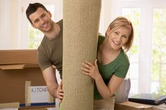 Portrait of couple moving house. Holding carpet rolled up, smiling stock photography