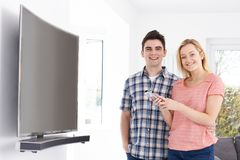 Portrait Of Young Couple With New Curved Screen Television At Ho. Portrait Of Couple With New Curved Screen Television At Home royalty free stock photography