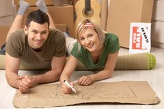 Portrait of couple planning their new home. Portrait of smiling couple lying on floor of new house making plan to furniture their home together on paper Royalty Free Stock Photography