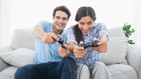 Portrait of a couple playing video games on the couch Royalty Free Stock Photography