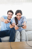 Portrait of a couple playing video games on the couch. Portrait of a beautiful couple playing video games on the couch Stock Photo