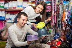 Portrait of couple purchasing pet bowls in petshop Stock Image