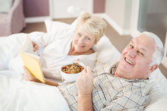 Portrait of couple reading book while having breakfast on bed Stock Images