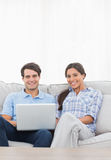 Portrait of a couple relaxing with a laptop Royalty Free Stock Photography