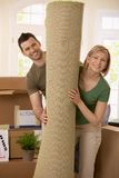 Portrait of couple with rolled up carpet. Portrait of smiling couple moving house, holding carpet rolled up, surrounded with boxes Stock Image
