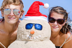 Portrait of couple and sand snowman on beach. Pretty couple having fun at beach with perfectly build snowman made out of sand wearing sunglasses Royalty Free Stock Photo