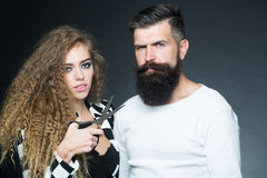 Portrait of couple with scissors. Couple of long-haired young beautiful women holding scissors with handsome bearded gray-haired men with moustache looking Stock Photos