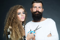 Portrait of couple with scissors. Couple of long-haired young beautiful women holding scissors with handsome bearded gray-haired men with moustache looking Stock Image