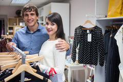 Portrait of couple selecting a dress while shopping for clothes Stock Photography