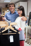 Portrait of couple selecting a dress while shopping for clothes. In apparel shop Royalty Free Stock Photo