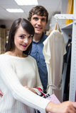 Portrait of couple selecting a dress while shopping for clothes. In apparel shop Royalty Free Stock Photography