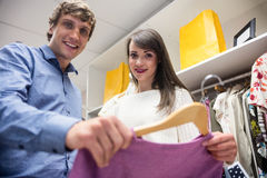 Portrait of couple selecting a dress while shopping for clothes. In apparel shop Stock Photography