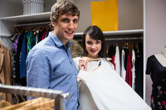 Portrait of couple selecting a dress while shopping for clothes Stock Photo
